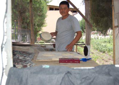 Der zweite Bäcker draussen legt den Teig auf ein feuchtes Kissen und klebt ihn an die Wand des Ofens